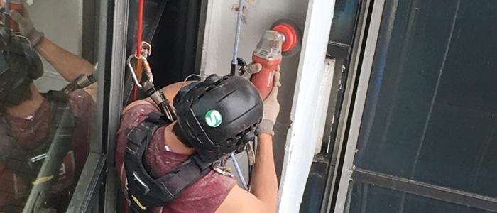 Technicien cordiste. Ponçage des poutres métalliques de la Tour de l'Unesco (Paris). Chantier réalisé avec les équipes d'Etair Ile de France.